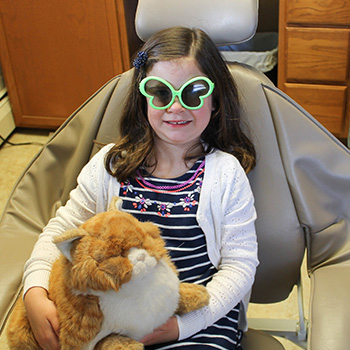 girl in dentist chair with sunglasses and stuffed animals